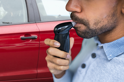 Man blowing into breathalyzer alcohol test device in front of red car