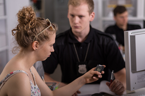Horizontal view of young woman holding breathalyzer in police station